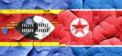 Swaziland flag with North Korea flag on a grunge cracked wall - stock illustration