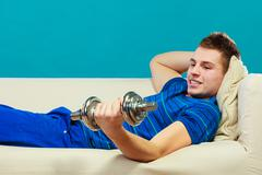 Young man fit body relaxing on couch after training - stock photo