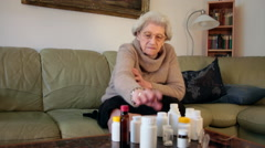 Sad sick depressed old woman on a couch at home with pills and drug bottles Stock Footage