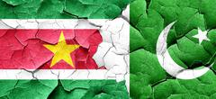 Suriname flag with Pakistan flag on a grunge cracked wall Stock Illustration