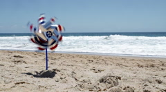 Spinning pinwheel in the sand at the beach HD Stock Footage