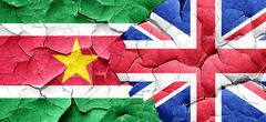 Suriname flag with Great Britain flag on a grunge cracked wall Stock Illustration