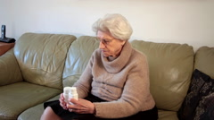 Pensive, upset, desperate, worried eighty year old lady holding pills bottle Stock Footage
