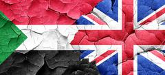 Sudan flag with Great Britain flag on a grunge cracked wall - stock illustration