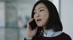 Japanese business woman in office talking on phone Stock Footage
