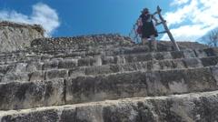 A gimbal shot of woman hiking up mayan ruins at ek balam Stock Footage