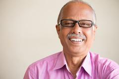 Closeup portrait, smart elderly man in pink shirt with dark eye glasses, spec - stock photo