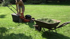 Gardener girl unload grass from lawn mower bag into barrow. 4K Stock Footage