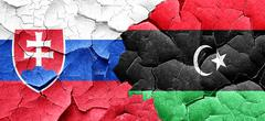 Slovakia flag with Libya flag on a grunge cracked wall - stock illustration