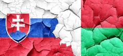 Slovakia flag with Madagascar flag on a grunge cracked wall Stock Illustration
