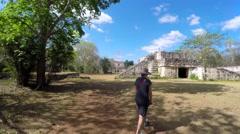 A gimbal shot of woman walking through mayan ruins at ek balam Stock Footage