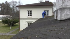 House cleaning service man spray moss with chemicals on roof Stock Footage