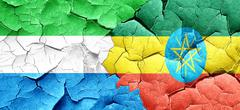 Sierra Leone flag with Ethiopia flag on a grunge cracked wall - stock illustration