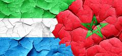 Sierra Leone flag with Morocco flag on a grunge cracked wall - stock illustration