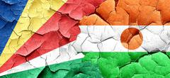 seychelles flag with Niger flag on a grunge cracked wall - stock illustration