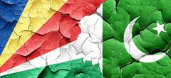 seychelles flag with Pakistan flag on a grunge cracked wall - stock illustration
