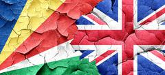 seychelles flag with Great Britain flag on a grunge cracked wall - stock illustration