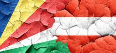 Seychelles flag with Austria flag on a grunge cracked wall Stock Illustration