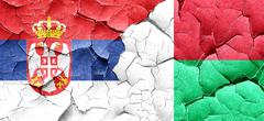 Serbia flag with Madagascar flag on a grunge cracked wall Stock Illustration