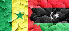 Senegal flag with Libya flag on a grunge cracked wall - stock illustration