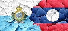 san marino flag with Laos flag on a grunge cracked wall - stock illustration