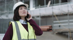 Construction supervisor speaking on phone at construction site Stock Footage
