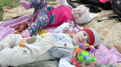 Children Babes lie on a blanket playing with a rattle and a picnic in the park Stock Footage