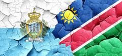 san marino flag with Namibia flag on a grunge cracked wall - stock illustration