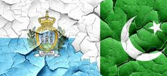 san marino flag with Pakistan flag on a grunge cracked wall - stock illustration