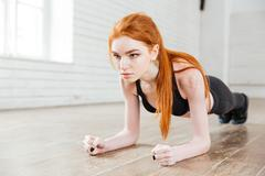 Concentrated beautiful fitness girl in sportwear exercising doing a plank - stock photo