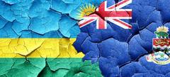 Rwanda flag with Cayman islands flag on a grunge cracked wall Stock Illustration