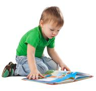 Little boy with a book sitting on the floor Stock Photos