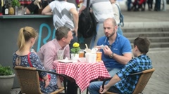 People sit at tables of street cafe - eat and drink beer Stock Footage