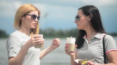 Two beautiful girls drink coffee  - paper cup - standing at the river Stock Footage