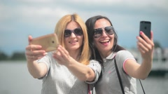 Two beautiful girls take photo selfie via mobile sell phone - day on river Stock Footage