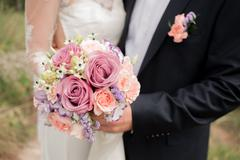 Wedding couple hugging, the bride holding a bouquet of flowers in her hand, the Stock Photos