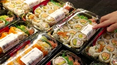 Woman buying sushi roll combo inside Price Smart foods store. Stock Footage