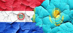 Paraguay flag with Kazakhstan flag on a grunge cracked wall - stock illustration