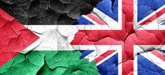 palestine flag with Great Britain flag on a grunge cracked wall - stock illustration