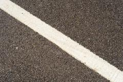 Single diagonal white traffic line painted on a grey tarmac road. Copy space  - stock photo