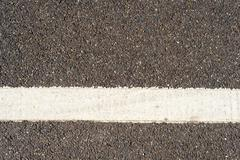 Single horizontal white traffic line painted on a grey tarmac road. Copy spac Stock Photos