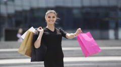 Sale, consumerism: Smiling young woman with shopping bags after mall - stock footage