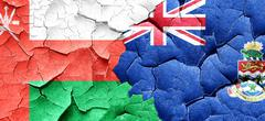 Oman flag with Cayman islands flag on a grunge cracked wall Stock Illustration