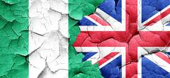 Nigeria flag with Great Britain flag on a grunge cracked wall - stock illustration
