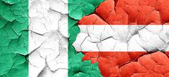 Nigeria flag with Austria flag on a grunge cracked wall Stock Illustration