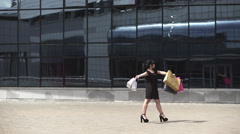 Sale, consumerism: Attractive woman with shopping bags after mall. Timelapse Stock Footage