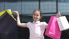 Child little girl young shopaholic with shopping bags near mall Stock Footage