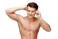 Handsome young man sniffing his armpit Stock Photos