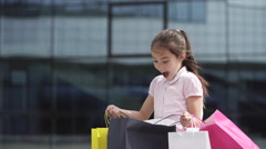 Child little girl young shopaholic with shopping bags near mall - stock footage