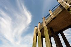 Wooden pier with tall beams and set against a blue sky with wispy white cloud - stock photo